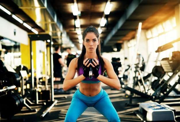 beautiful-focused-young-fitness-girl-doing-squats-with-kettlebell-looking-into the camera at a gym - learning and practicing to squat like a pro